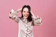 La mujer morena joven atractiva hermosa sonríe feliz y ríe Retrato del estudio aislado en fondo rosado foto de archivo libre de regalías