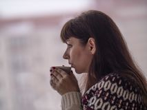 La mujer morena joven bebe el café y mira hacia fuera la ventana cuidadosamente foto de archivo