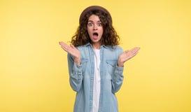 La mujer morena joven con el pelo rizado abrió su boca en una sorpresa, sobre fondo amarillo fotografía de archivo libre de regalías