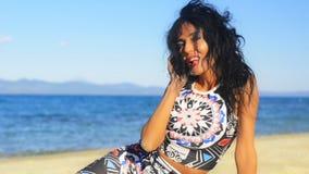 La mujer morena joven en la playa y anuncia una llamada a su teléfono celular metrajes