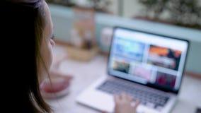 La mujer morena joven está hojeando el sitio, compras en línea con el cuaderno y el café de consumición en sitio claro en hogar metrajes