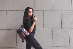 La mujer morena joven hermosa con la mochila se vistió en equipo negro foto de archivo libre de regalías