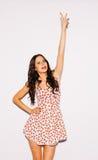 La mujer morena joven hermosa en un vestido corto del verano levantó para arriba su mano con una muestra Victoria indoor Color ca Fotografía de archivo libre de regalías