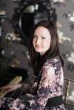 La mujer morena joven hermosa en vestido juega el piano Foto de archivo libre de regalías