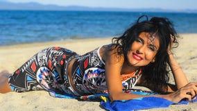 La mujer morena joven hermosa pone en la playa y ríe con su teléfono móvil metrajes