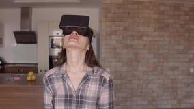 La mujer morena joven que usa su VR enmascara en casa Vidrios asequibles de la realidad virtual en la acción vídeo del steadicam  almacen de video