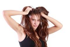 La mujer morena joven rasga su pelo y mira la cámara Imagen de archivo