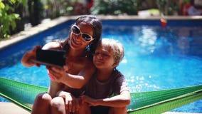 La mujer morena joven se sienta con su hijo en selfie de las tomas de la hamaca con el teléfono por la piscina Familia feliz, vac metrajes