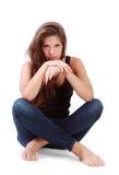 La mujer morena joven se sienta en piso con las rodillas dobladas Imagen de archivo