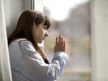 La mujer morena joven triste mira hacia fuera la ventana foto de archivo