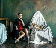 La mujer morena rica de la belleza en marcos vacíos cercanos interiores de lujo, moda que lleva viste, gente bastante real de la  Imagen de archivo