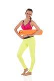 La mujer morena sonriente en las polainas amarillas de neón de los deportes y el sujetador rosado que se colocaban con la naranja Foto de archivo