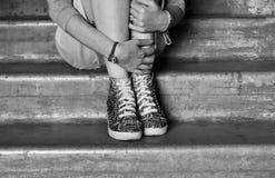 La mujer/la muchacha se sienta en los pasos, el esperar, abrazándose con sus manos detrás de sus piernas Foto de archivo