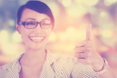 La mujer muestra el pulgar para arriba con el fondo de la falta de definición Fotografía de archivo
