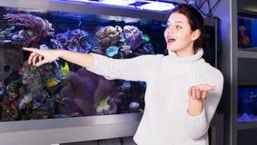 La mujer muestra el surtido de tipos de acuarios Foto de archivo