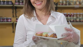La mujer muestra la caja con las tortas de la elaboración de la cerveza metrajes