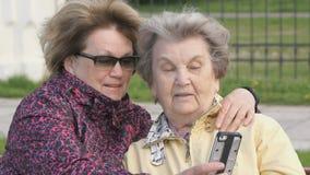 La mujer muestra la foto a la mujer mayor que usa el teléfono móvil metrajes