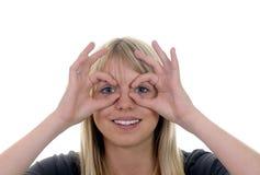 La mujer muestra los prismáticos Fotografía de archivo libre de regalías