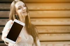 La mujer muestra a pantalla negra el teléfono elegante, móvil en el foco, mofa para arriba Fotos de archivo libres de regalías