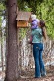 La mujer muestra a su hija el alimentador del pájaro fotografía de archivo libre de regalías