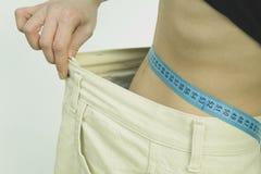 La mujer muestra su pérdida de peso Fotos de archivo libres de regalías