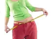 La mujer muestra a su pérdida de peso llevando los pantalones grandes viejos Foto de archivo