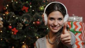 La mujer muestra su pulgar para arriba cerca del árbol de navidad almacen de video