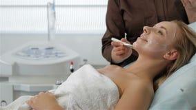 La mujer muestra su pulgar para arriba con la máscara facial almacen de video