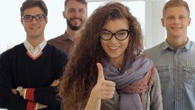 La mujer muestra su pulgar para arriba delante de tres hombres en la oficina almacen de video