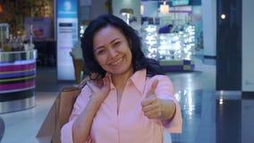 La mujer muestra su pulgar para arriba en la alameda fotos de archivo libres de regalías