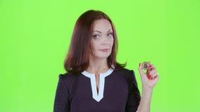 La mujer muestra un bitcoin de la moneda de oro Pantalla verde metrajes