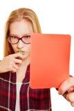 La mujer muestra una tarjeta roja como advertencia Imagenes de archivo
