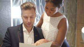 La mujer multirracial joven está señalando en procedimiento de la moda en precio al hombre alegre en el centro de la belleza almacen de metraje de vídeo