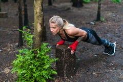 La mujer muscular que hace pectorales en la calle del parque se resuelve Fotos de archivo libres de regalías
