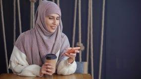 La mujer musulmán alegre adulta está leyendo SMS en teléfono móvil y está sonriendo en café almacen de video