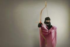 La mujer musulmán asiática hermosa con velo quiere tirar una flecha Fotografía de archivo