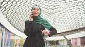 La mujer musulmán bonita en un hijab con una mochila se está colocando en un centro comercial y está hablando en el teléfono almacen de metraje de vídeo