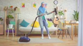 La mujer musulmán en hijab está engañando alrededor con una danza del aspirador como guitarrista metrajes