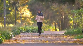 La mujer musulmán en hijab va a activar en parque otoñal almacen de video