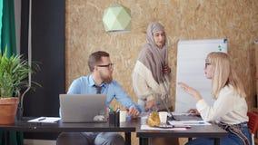 La mujer musulmán está ayudando a su varón y colegas femeninos en oficina almacen de video