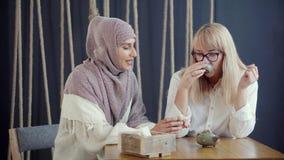 La mujer musulmán está hablando alegre con su amigo rubio en el café, bebiendo té almacen de metraje de vídeo