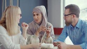 La mujer musulmán está hablando historias a su varón y amigos femeninos en café metrajes