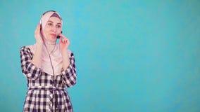 La mujer musulmán hermosa joven con las auriculares del teléfono comunica almacen de video