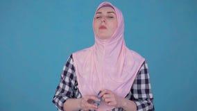 La mujer musulmán joven en ataque de asma del hijab, utiliza el espray almacen de metraje de vídeo