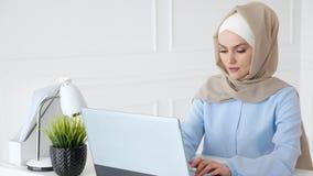 La mujer musulmán joven está mecanografiando en el funcionamiento del ordenador portátil en oficina metrajes
