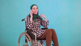 La mujer musulmán joven inhabilitó en una silla de ruedas que hablaba en el teléfono en un fondo azul almacen de video