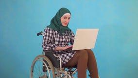 La mujer musulmán joven inhabilitó en una silla de ruedas utiliza un ordenador portátil en un fondo azul almacen de metraje de vídeo