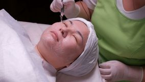 La mujer musulmán relajada con los ojos se cerró durante un procedimiento terapéutico del disincrustation Muchacha asiática en la almacen de metraje de vídeo