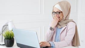 La mujer musulm?n cansada en vidrios en el final del d?a laborable est? mecanografiando en el ordenador port?til almacen de video