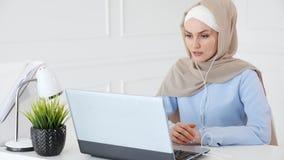 La mujer musulm?n est? aprendiendo ingl?s en auriculares en l?nea usando el ordenador almacen de metraje de vídeo